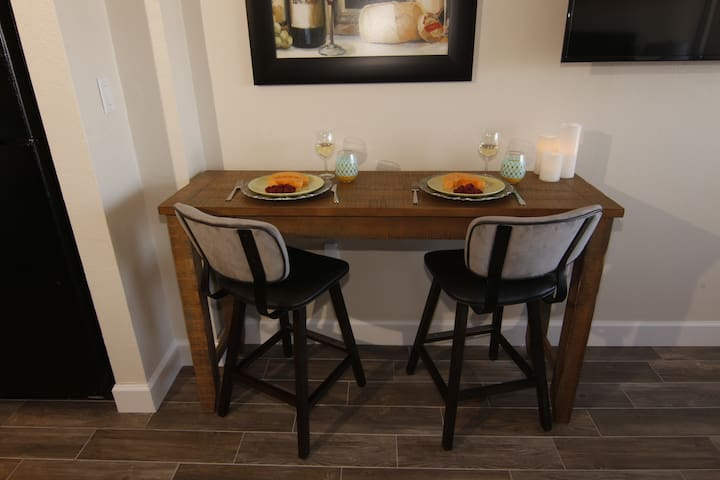 The picture shown here is with the Bistro table back leaf closed.  With the leaf open, there is room for an additional person to sit and eat.