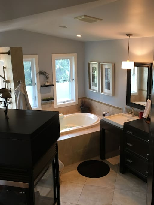 Huge ensuite with an incredible shower with a rain head and an air-jet tub with chromatherapy, fireplace, dual wading sinks
