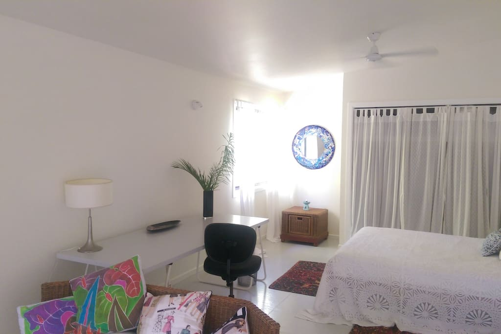 large studio style room with desk and large space for yoga practice