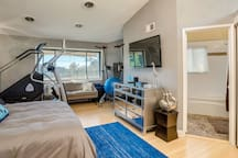 The guest bedroom features a queen size bed, views of the canyon, attached bath, desk/workspace, and large Smart TV.