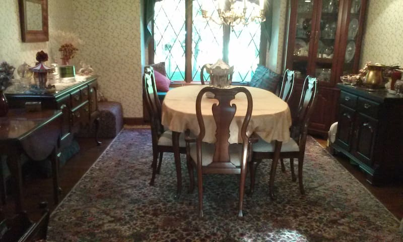 Dining Room with Bay window looking onto wooded lawn.