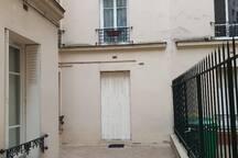 La porte fenêtre fermée avec le volet métallique dans la cour intérieure sécurisée.