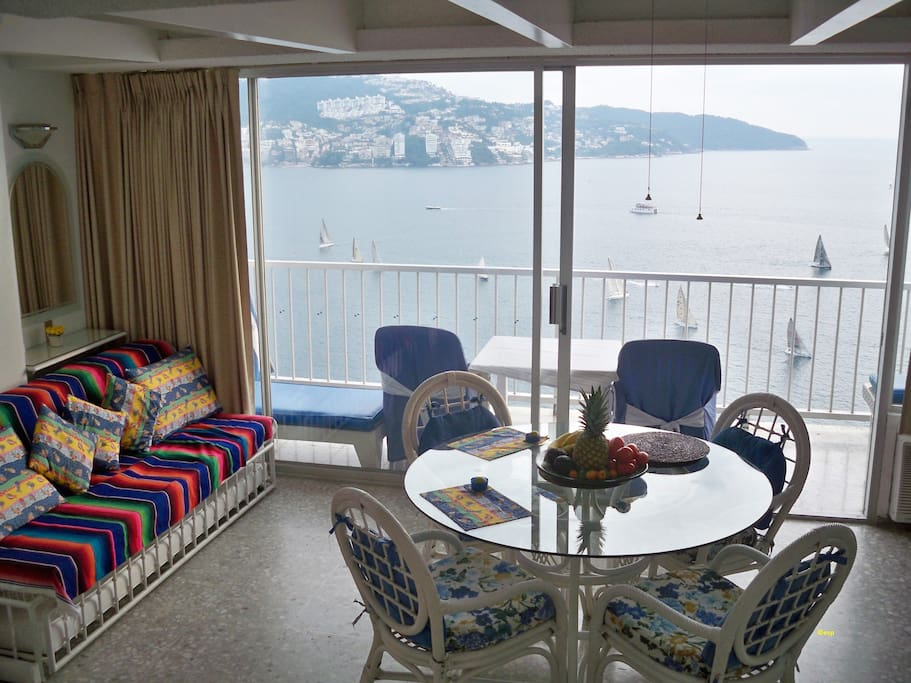 Mexican wicker chairs, plate glass dining table, sailboats in Acapulco Bay