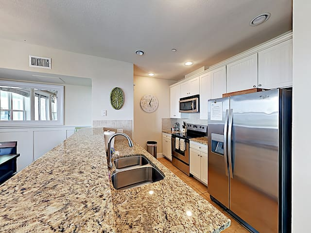 A full suite of stainless-steel kitchen appliances includes a microwave and electric range.