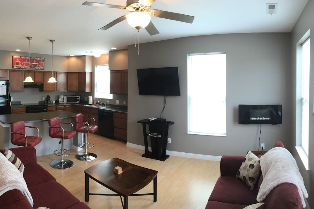 """Panoramic photo of family room with 50"""" TV and kitchen..."""