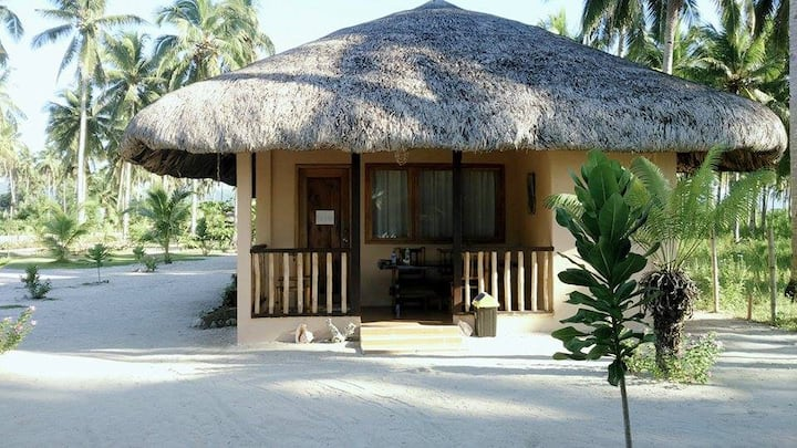 A family room just in front of a white sand beach