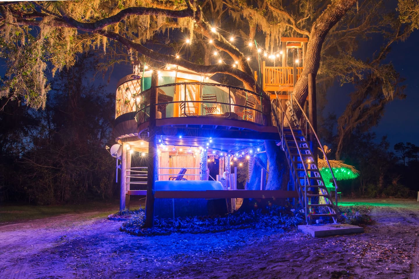 Tree house at night, blue lights over hot tub