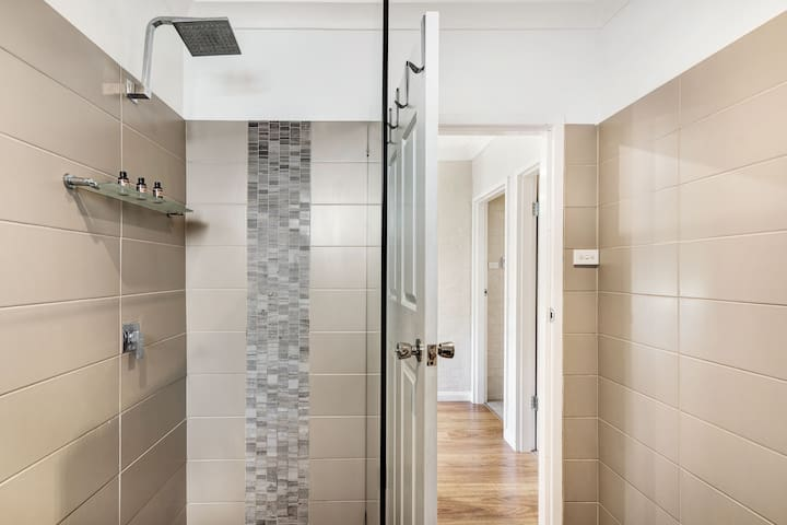 Large size shower recess with essential toiletries provided.