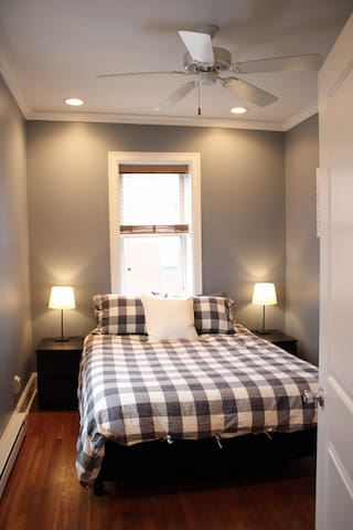 Full-size Tempurpedic mattress, new bedding, modern window AC unit, overhead fan, and a clothing rack with hangers.