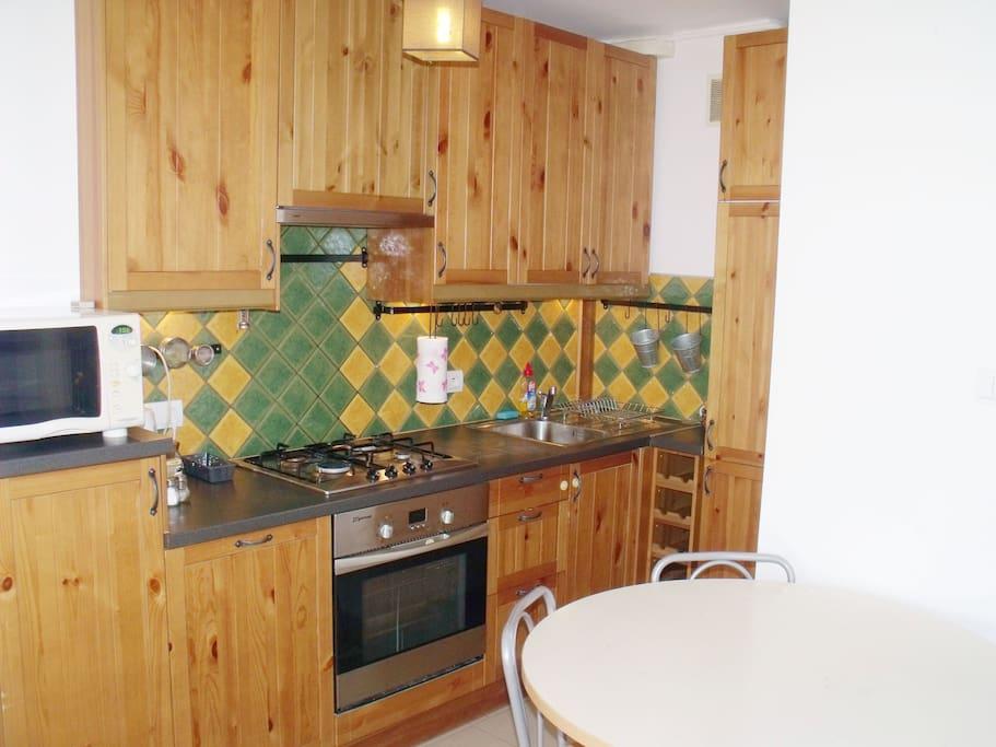 Kuchnia (kuchenka gazowa z piekarnikiem, lodówka, mikrofalówka).