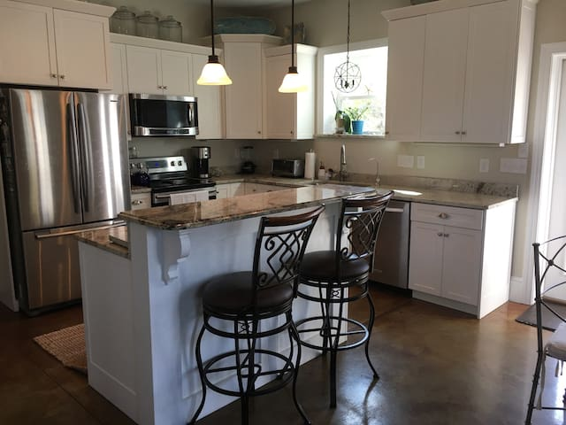 Convenient ground level kitchen featuing eat at bar and dining table