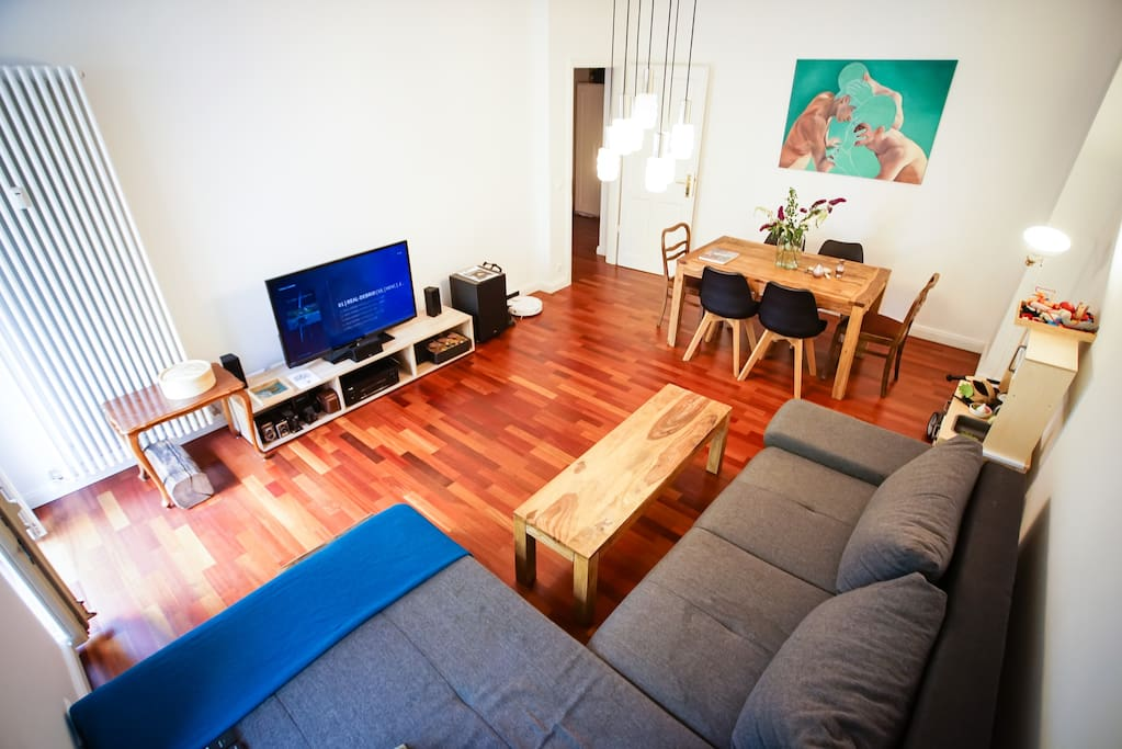 Living room with big couch, TV, dining table and access to the first balcony