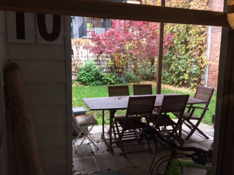 Jardin clos fleuri et verdoyant avec barbecue