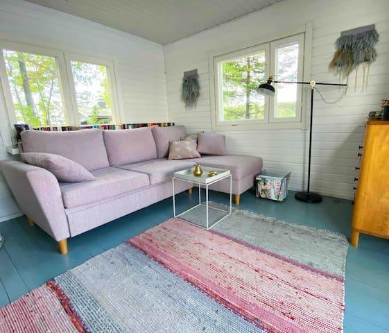 Main cabin downstairs with fireplace, large dining table and a double sofa bed. / Päämökin alakerta jossa takka, iso ruokapöytä ja vuodesohva.