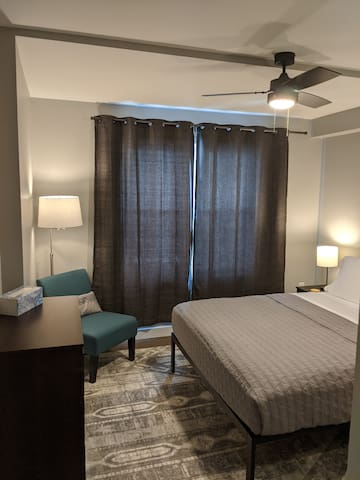 The second bedroom also has a comfortable chair and dresser.