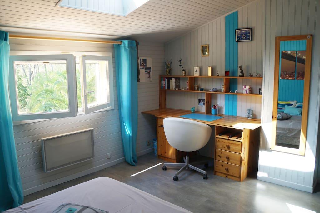La chambre est très lumineuse avec bureau et étagères