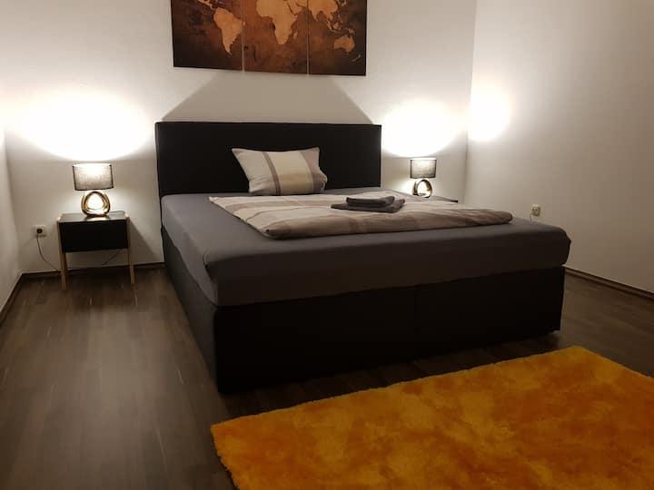 Stilvolles Zimmer mit Boxspringbett und Smart-TV