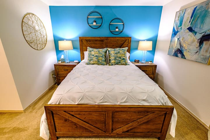 """Master bedroom Includes: Alarm clock with USB outlet, white noise machine, 43"""" Roku Smart TV, chest of drawers and space fan."""