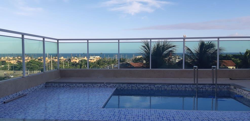 Confortável quarto e sala com piscina e vista mar