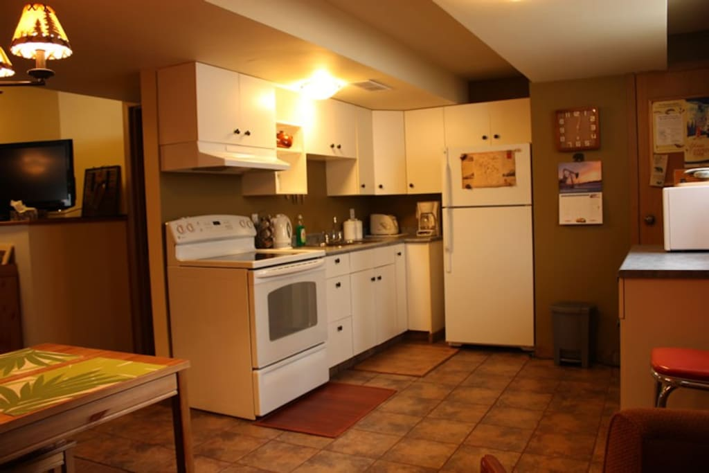 Large kitchen with full sized appliances, fridge, freezer, stove and microwave, pots, pans, dishes, utensils