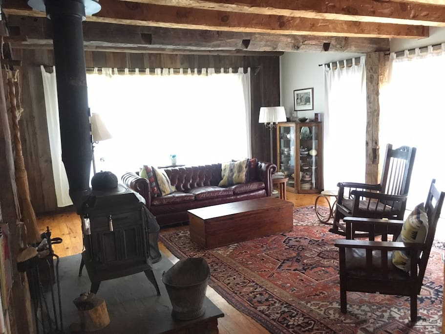The double height living room has a wood stove, bay window over the pond and french doors opening onto the deck. Furnished with comfortable and beautiful antiques