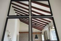 Vistas desde los espejos de los techos en salón con vigas de madera maciza y altura de 3 a 6 metros