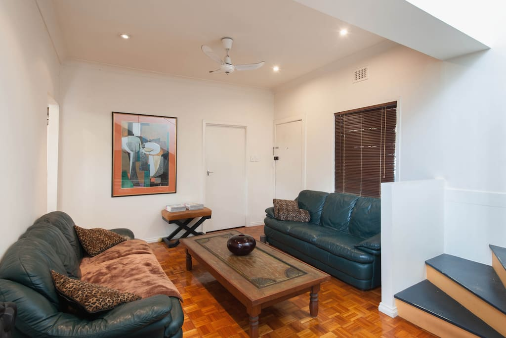Simple and comfortable living room with large TV, DVD and CD player.