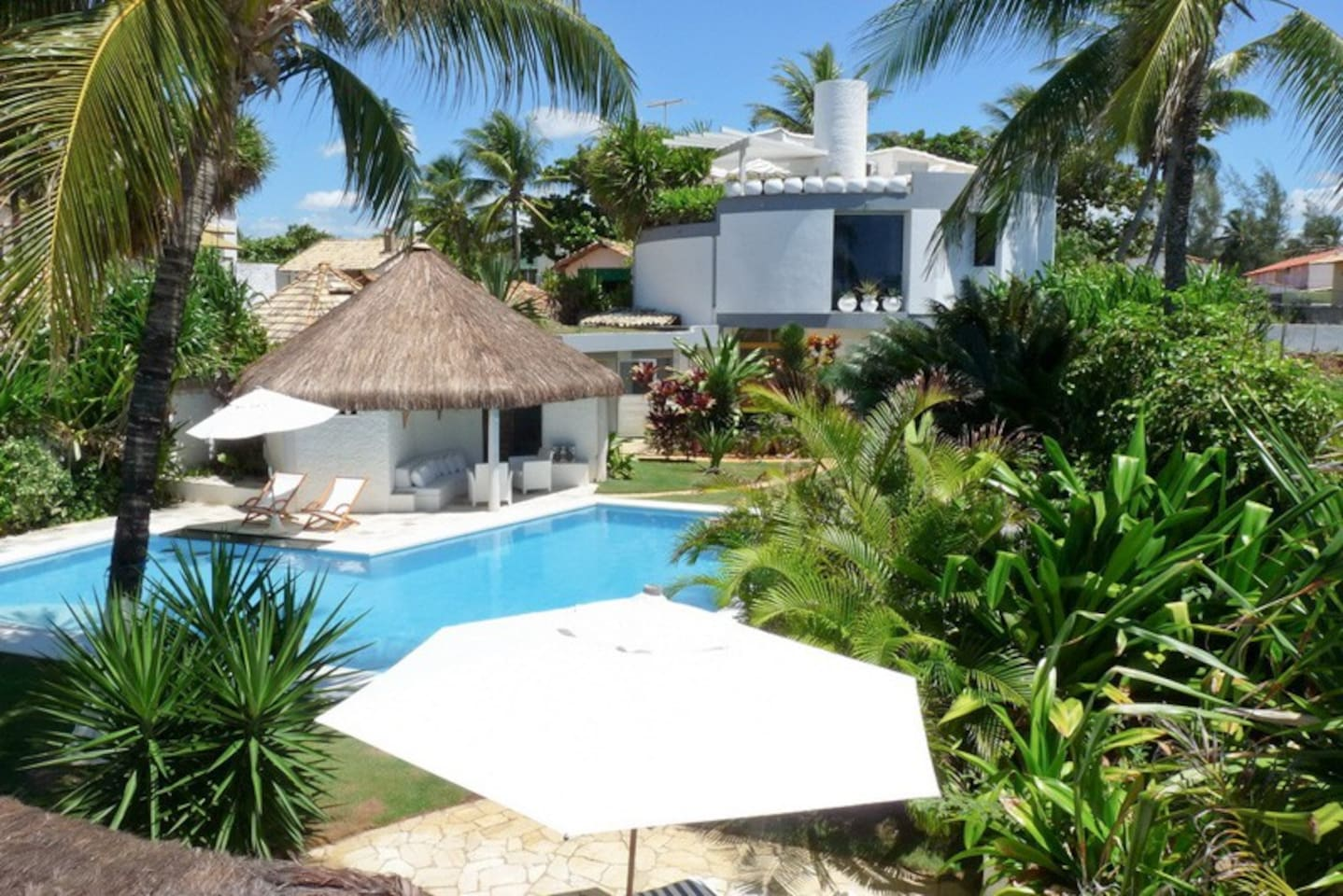 Lush tropical garden, cabana & swimming pool frame this upscale 4 bdrm beach villa