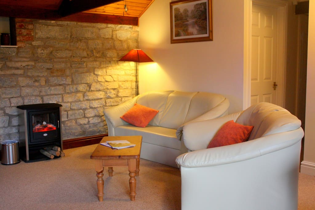 Beams and original stone walls give the lounge a cosy appearance