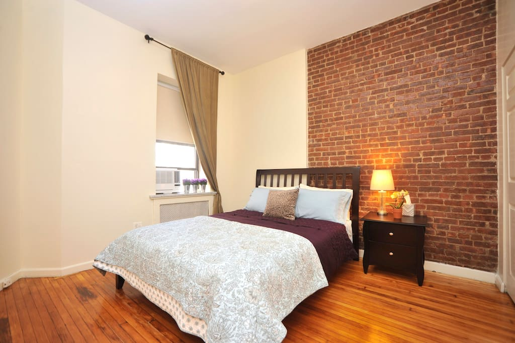 Master bedroom with queen size bed and original exposed brick wall and hardwood floors.