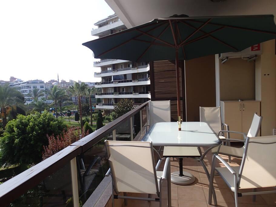Stor terrasse med spiseplass og parasoll