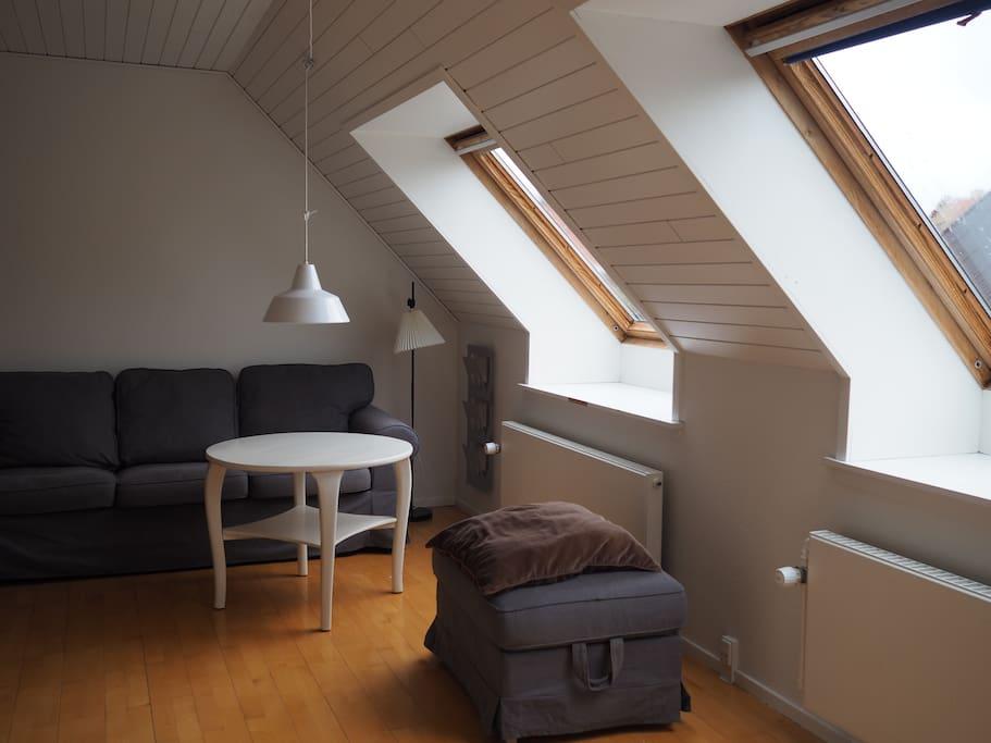 Stort værelse med dobbeltseng, barneseng og sofa.