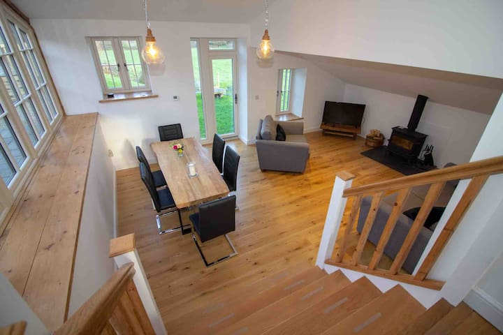 5 steps lead down to the lounge/diner which has a tv, Wood burner and patio doors leading to the orchard