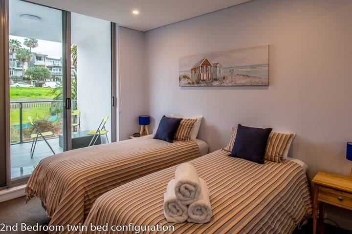The 2nd bedroom can be made up with twin beds. There are 2 bedside tables with lamps and an alarm clock.  A full size built in wardrobe.  Access to the 2nd balcony.