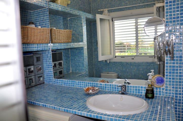 Baño del dormitorio principal con ventana al jardín y al mar