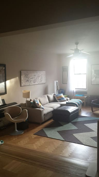 HUGE and sunny living room with weighted keyboard and smart TV.