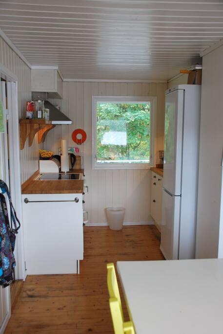 Kjøkken med komfyr, kjøleskap m/fryseskap, kaffemaskin og vannkoker.