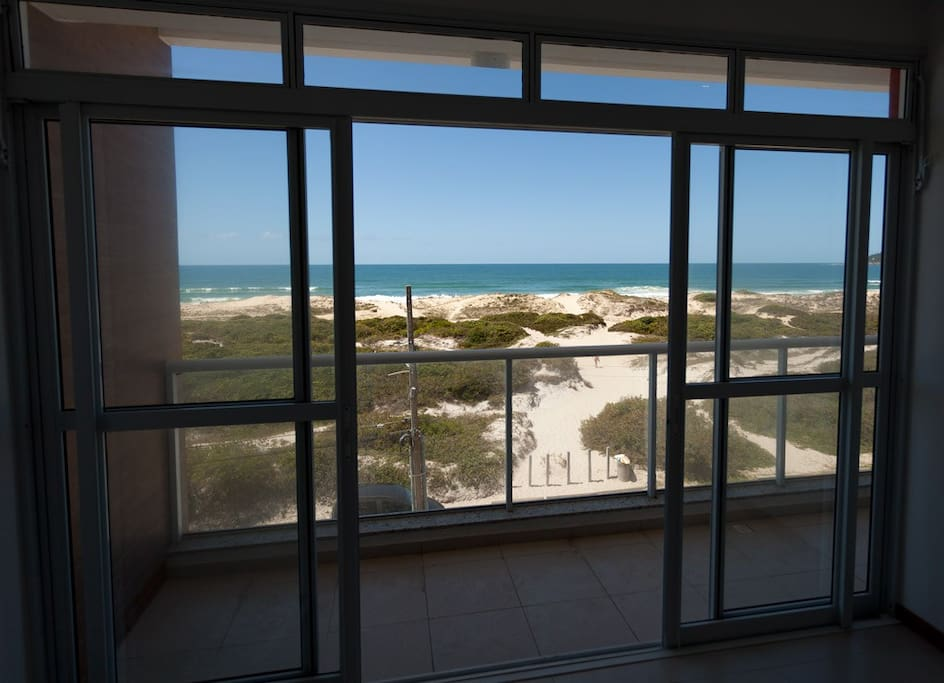 View from Living/Dining Room across balcony and dunes to sea.