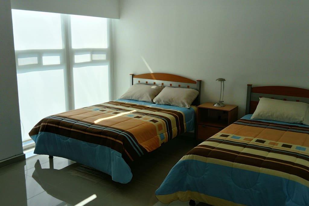 Habitación amplia con una cama matrimonial y una individual