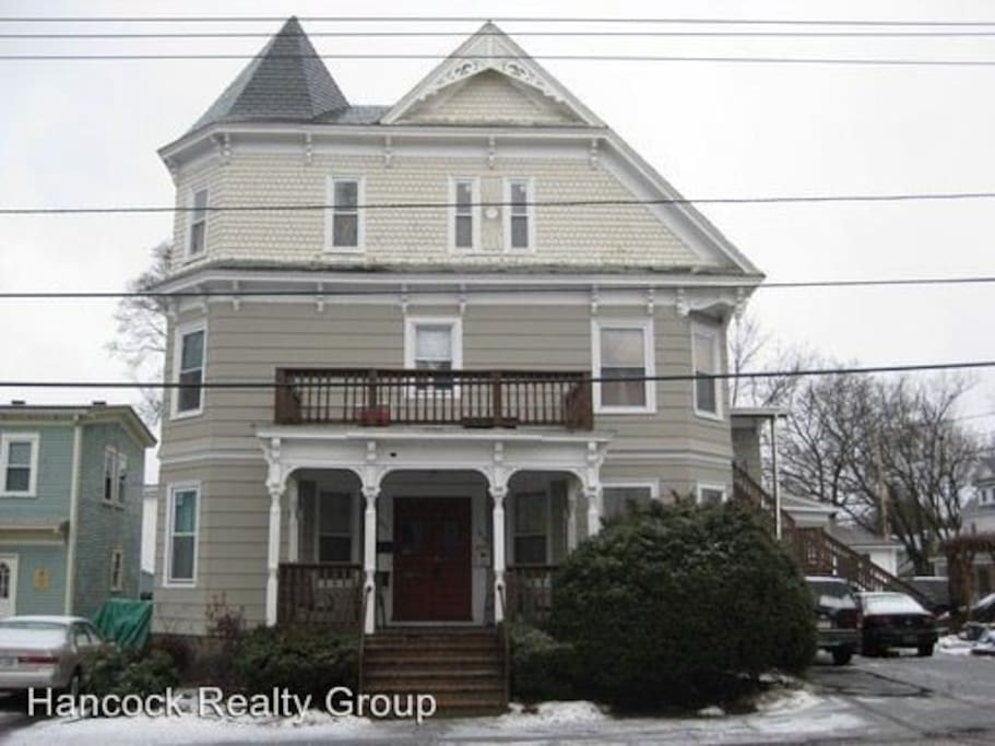 Recent picture of building. Second and third floor are one single unit; very large space. Two available bedrooms both on second floor. Third floor occupied by three residents. Two parking spaces available, as well as street parking.