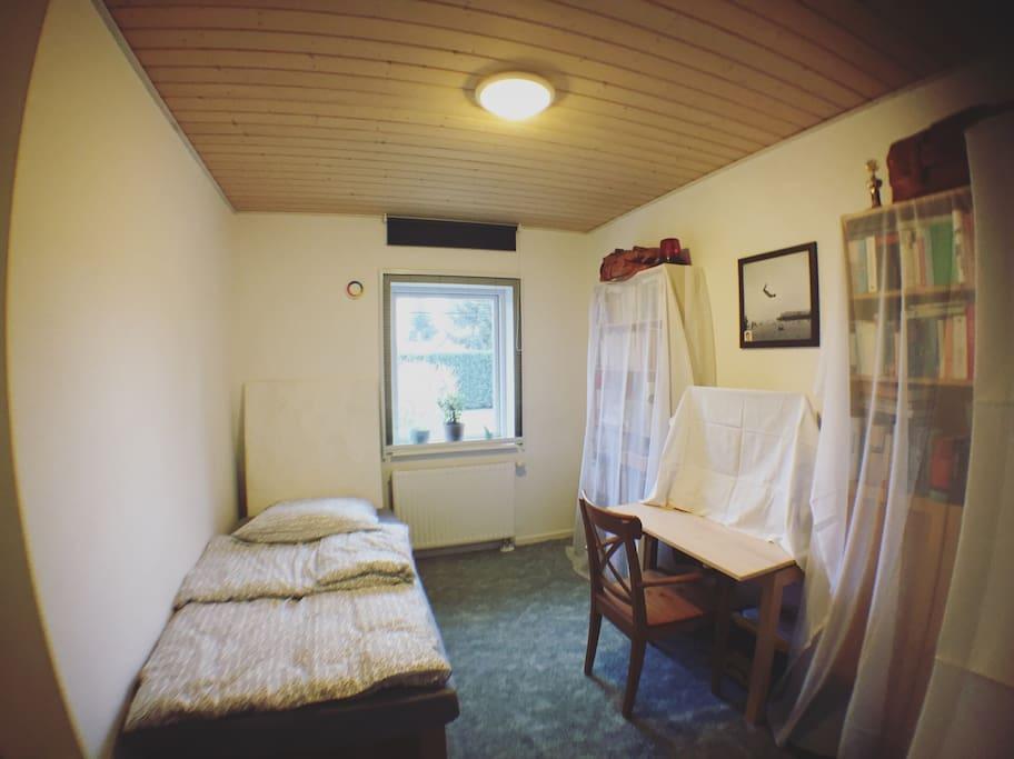 Kleines Zimmer mit Fenster und Schreibtisch