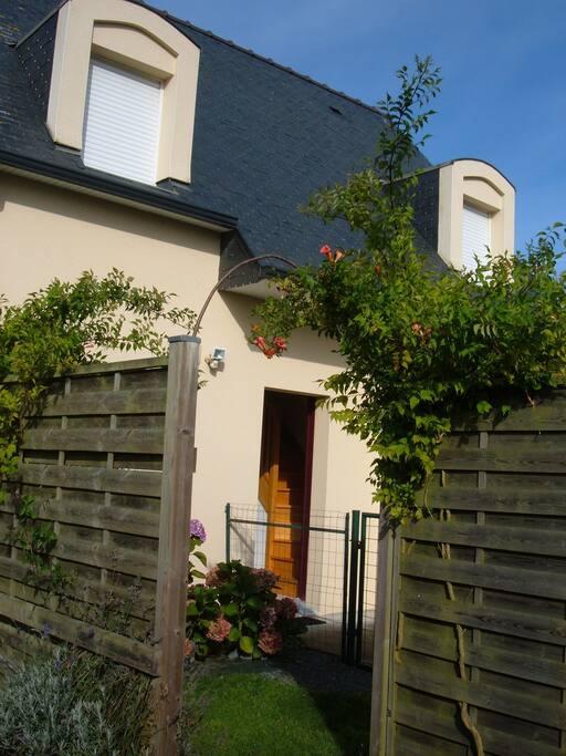 La porte d'entrée de la maison avec son hall et l'escalier pour l'étage