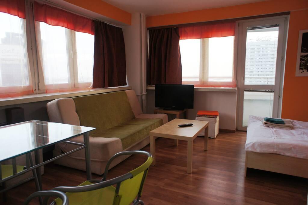 Łózko, sofa i stół z 4 krzesłami.