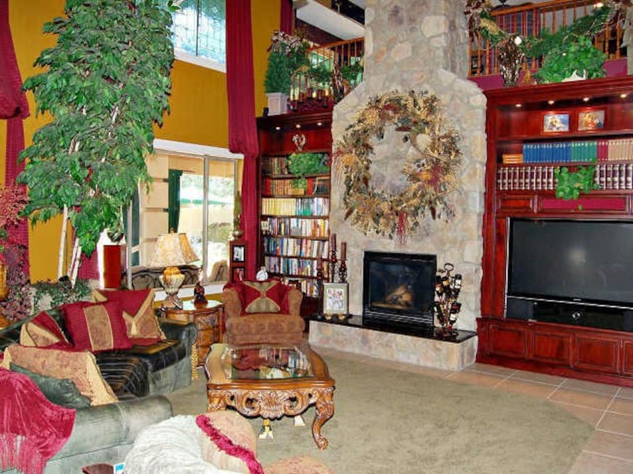 Cozy living room with grand fireplace and built-in cherry book cases