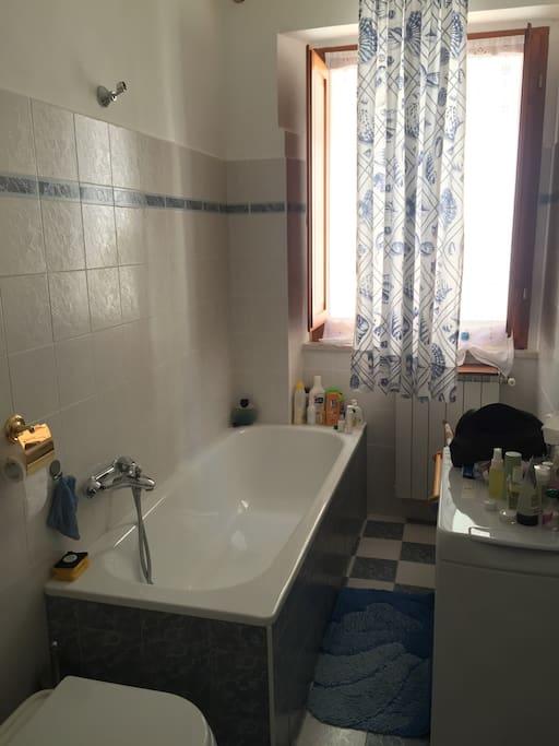 Salle de bain avec baignoire meuble vasque et une machine à laver
