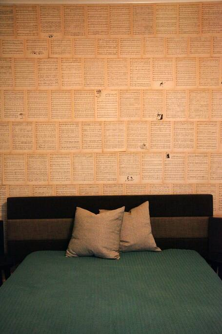Queen size bed with antique sheet music wallpaper.