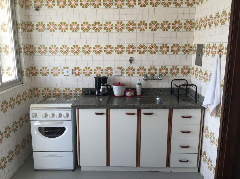 Cozinha equipada com fogão, geladeira, microondas, cafeteira e tostadeira.