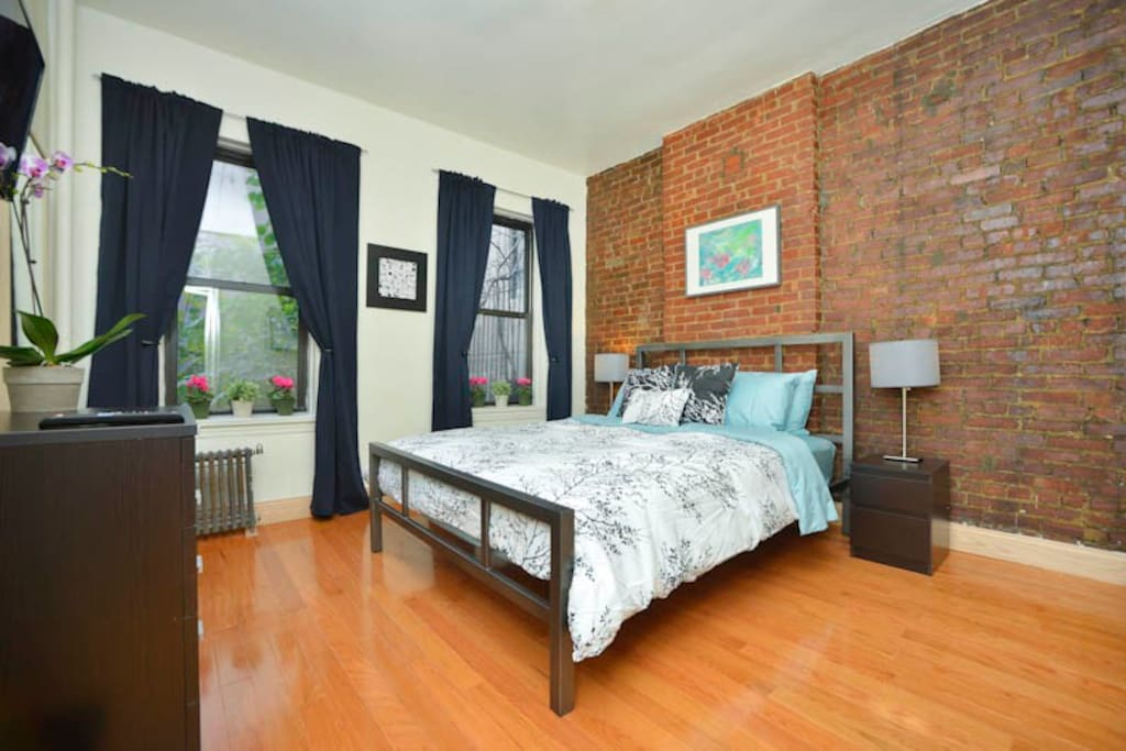 Queen-size Bedroom with original exposed brick wall.