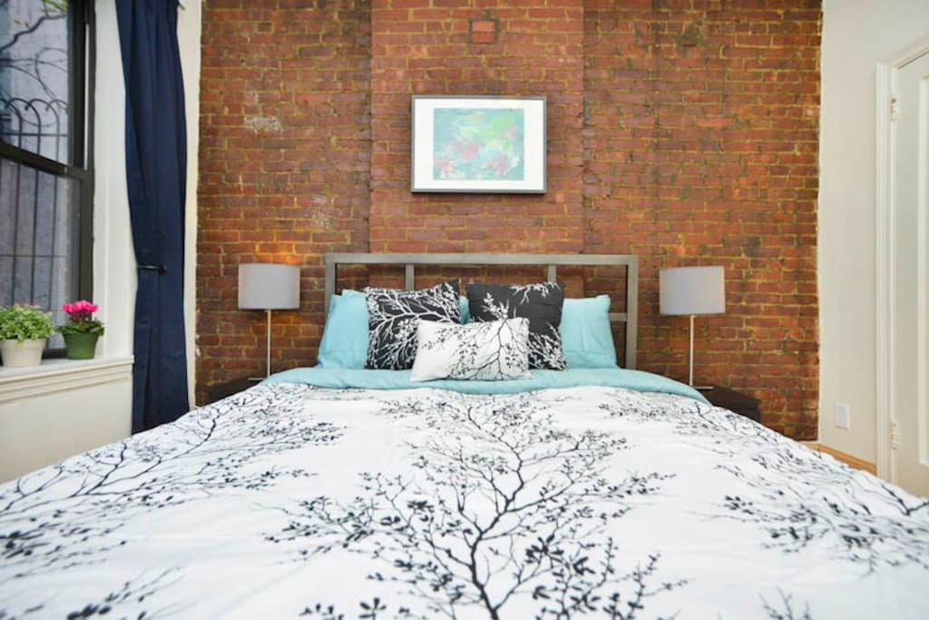 Contemporary steel-fame bed against original brick wall
