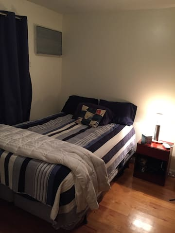 Freshly made queen sized bed  in a spacious bedroom with light and noise blocking curtains.